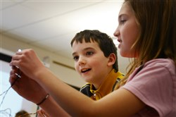Tegan Welsh, 10, and Ilijana Hasak, 11, work on building a robot during an after-school program based on robotics, technology and coding Monday at Quaker Valley Middle School in Sewickley.