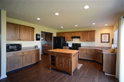 The kitchen has oak cabinets, a stainless-steel corner sink and black appliances.