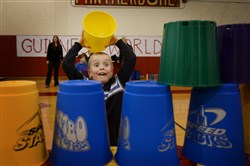First-grader Konrad Grossheim stacks buckets Thursday during a fast-paced stacking exercise as part of the Guinness World Records Day event at Sewickley Academy.