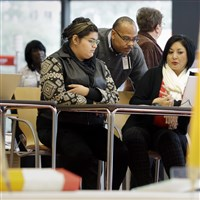 Affordable Care Act health insurance marketplace navigators Leticia Chaw, right, and Herb Shook, center, help get information for Jennifer Sanchez to re-enroll in a health insurance plan Friday in Houston.