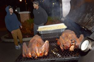 Turkeys finish smoking on the Blowfish BBQ grill outside The Brew Gentleman brew pub in Braddock where head brewmaster Brandon Capps, plans to brew a special Thanksgiving day beer using the turkeys.
