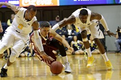 West Virginia guard Jevon Carter, left, reacahes for the  the loose ball alongside teammate Jonathan Holton, right as Lafayette guard Monty Boykins tries to regain control Sunday in Morgantown, W.Va.