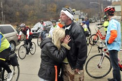 Beth Ann Banks, the mother of Taylor Banks — who was struck by a vehichle and killed while riding his bicycle home on Oct. 31 — holds onto friend Craig Morrow on Sunday as motorcyle riders and bicyclists ride to the ghost bike dedicated to Mr. Banks.