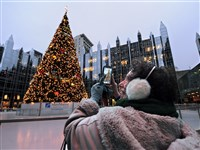 Peggy Zezza of Forest Hills snaps a photo of the Christmas tree at the ice rink at PPG Place, Downtown, which will open for the season during Light Up Night Friday.