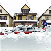 Lori Weishaar shovels snow from around her vehicle on Thursday after the catastrophic snowstorm in Buffalo, N.Y.
