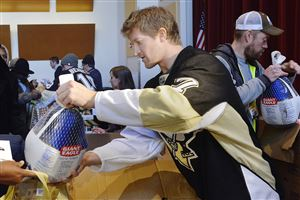 Pittsburgh Penguins defenseman Paul Martin, second right, during a Thanksgiving distribution at the Hill House Kaufmann Auditorium, November 20. The event, a partnership between the Penguins and the Greater Pittsburgh Community food Bank, served 100 families.