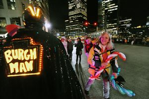 Carol Forbes of Cecil Twp., with her grandson John Cox slung on her back, takes in the sights and sounds of Pittsburgh's 54th annual Light Up Night.
