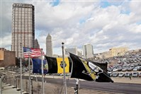 Wind-swept flags at the Consol Energy Center on Monday frame the parking lot where the Civic Arena once stood.
