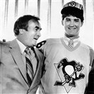 Mario Lemieux dons a Penguins sweater and stands with Penguins GM Eddie Johnston after signing a mulit-year contract with Pittsburgh June 19, 1984.