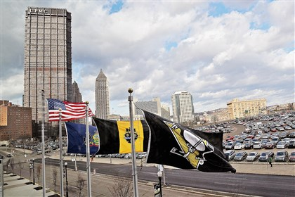 Wind-swept flags at Consol Energy Center frame the parking lot where the Civic Arena once stood in Pittsburgh's Hill District.