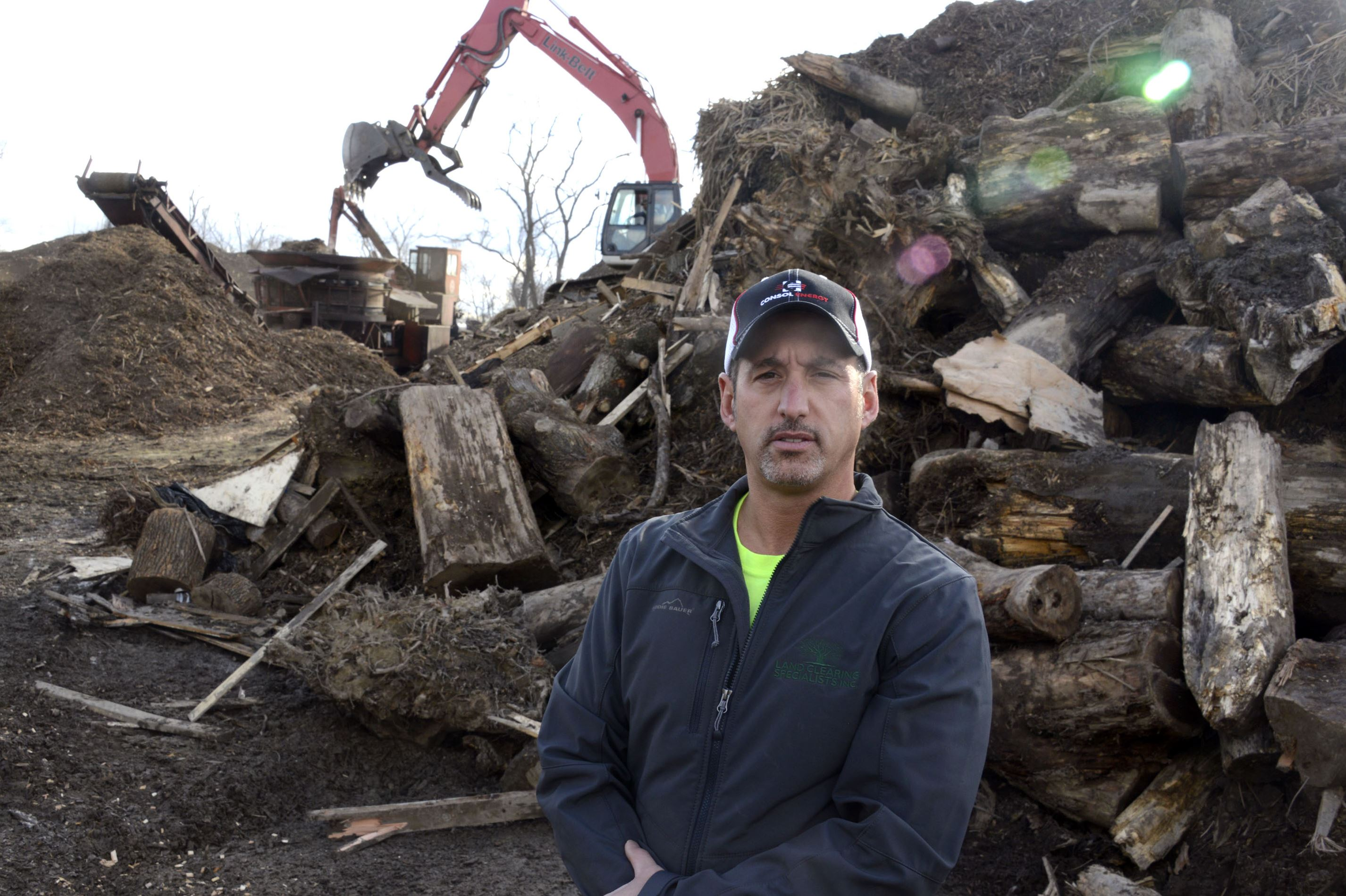 "20141124dsLandclearing1202Biz01 Eric Vaccarello , president of Land Clearing Specialists Inc., stands near stumps and woodwaste placed in a ""grinder"" making wood chips. Vaccarello owns one of the largest land-clearing and reclamation services operating in the Marcellus and Utica Shales areas."