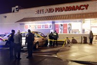 Pittsburgh police investigate the scene where a pregnant woman died after an elderly man drove up on the sidewalk and pinned her against the wall, outside the Rite Aid Pharmacy on the North Side.