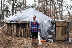 Dylan Miller, a senior at Juniata College, outside the hut he constructed of downed trees, leaves and other materials.