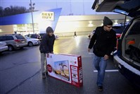 "Nate Murano, left , of Lawrence, Kan., and Kent Diasabeygunawardena of the North Side load up a 55"" TV from  Best Buy  in Ross Twp. on Thursday."