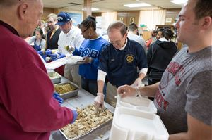 "Volunteers Tony Den Uyl, left, Ted Meinert, center, and Jordan McKim, right, prepare meals for the ""Stuffed With Love"" program Thursday at St. Mary's Church on the South Side. This program provides families in need with meals delivered by Pittsburgh police officers."