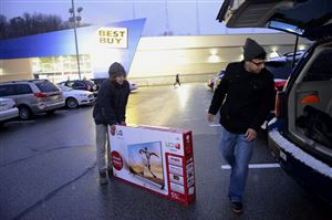 Nate Murano, left , of Lawrence, Kan., and Kent Diasabeygunawardena of the North Side load up a 55-inch TV from Best Buy in Ross.