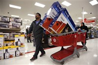 Ahmad Ali and his wife, Ghalzal, of Portland, Maine, look to get in line to pay for three flat-screen televisions while shopping at a Target store just after midnight on Black Friday.