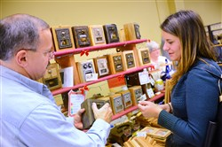 Paul Fruehan, owner of Wood-N-You Like It from West Mifflin shows an antique post office box to Lauren Pusateri of Castle Shannon.