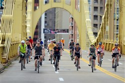 Bicyclists participating in the Pedal Pittsburgh event cross the Roberto Clemente bridge onto the North Side. A BetaBurgh project this summer will capitalize on the growing popularity of cycling.