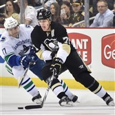 The Penguins' Evgeni Malkin is defended by the Canucks' Radim Vrbata during a December game at Consol Energy Center.