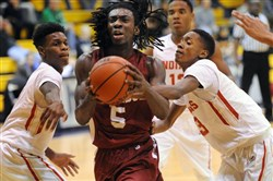 Ambridge's Daylon Carter splits two Penn Hills defenders in a 70-60 win Friday at Mars.