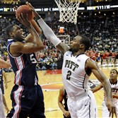 Pitt's Michael Young blocks a shot by Duquesne's Darius Lewis in the first half at Consol Energy Center Friday night, December 5, 2014.