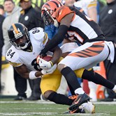Antonio Brown pulls in a pass as he's taken down by Bengals' Darqueze Dennard in the third quarter at Paul Brown Stadium Sunday afternoon, December 7, 2014.