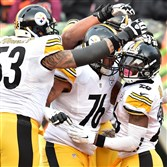 Teammates congratulate Le'Veon Bell after he scored in the fourth quarter Sunday against the Bengals at Paul Brown Stadium in Cincinnati.