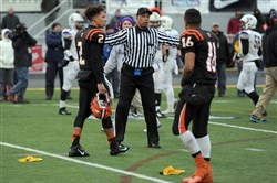 An official separates players as Clairton and Bishop Guilfoyle teammates tussle at the end of the PIAA Class A championship at Hersheypark Stadium last Friday.