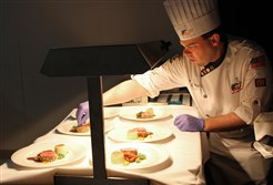 Shawn Culp putting the finishing touches on the ACF Culinary Team USA ' entrée of Roasted Beef Sirloin with Sweetbread and Smoked Tongue, Truffle-celeriac Dauphinoise, Woodland Mushroom Variety, Braised Carrot, Semolina Dumpling, Jus Lie.