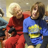 Resident Alice Lauffer, 97, talks Saturday with scout Xavier Molgaard, 8, of Polish Hill, as scouts visit seniors at Beatty Pointe Village, a UPMC Senior Community.