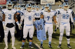 Central Valley players Jordan Whitehead, Skyler Cron, Preston Johnson and Rocco Martini hold the jersey of teammate Dominick Treemarchi ahead of the coin toss before their game against Archbishop Wood in the PIAA Class AAA Championship.