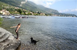 Silvia Givera with her dog, Diego, on the banks of Lake Como.