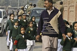 A plainclothes security officer escorts students rescued from a nearby school during a Taliban attack in Peshawar, Pakistan, Tuesday.
