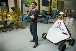 John Thornton, CEO of Astrobotic, stands in front of the company's Griffin Lander, left, and the Red Rover, right, at its headquarters in the Strip District.