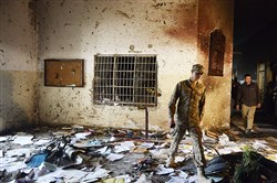A Pakistani soldier walks amidst the debris in an army-run school Wednesday after an attack by Taliban militants in Peshawar on Tuesday.