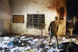 A Pakistani soldier walks amid the debris in an army-run school Wednesday after an attack by Taliban militants in Peshawar on Tuesday.
