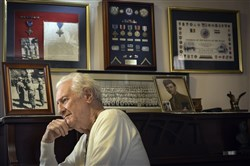 Al Darago, 89, a Battle of the Bulge veteran, sits at home in Parkeville, Md., where he hangs his Distinguished Service Cross. During the battle, he said he blew up a tank with a bazooka.