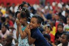 First-graders Davaisha Bush, left, and Miranda Diggs react as their names are called during the United Way Be There 30-Day Challenge ceremony honoring students' attendance at Pittsburgh Faison K-5 in June. Faison K-5 is one of five priority schools in Pittsburgh that received federal School Improvement Grants.