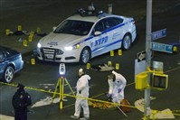 Police investigate the scene where two New York City police officers were killed Saturday afternoon as they sat in their marked police car on a Brooklyn street corner.