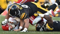 Steelers' Cameron Heyward takes down Kansas City Chiefs quarterback Alex Smith in the first quarter at Heinz Field today. Smith was sacked six times during the game.