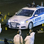 Bulletproof vests lie on each side of an NYPD patrol car as investigators work at the scene where two NYPD officers were shot in the Bedford-Stuyvesant neighborhood of the Brooklyn borough of New York on Saturday, Dec. 20, 2014. Police said an armed man walked up to the officers sitting inside the patrol car and opened fire before running into a nearby subway station and committing suicide. Both police officers were killed.