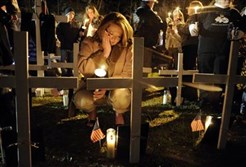 In this file April 5, 2011, file photo, Jami Cash, daughter of dead coal miner Michael Elswick, attends a vigil following the Upper Big Branch memorial service in Whitesville, W.Va., for the 29 coal miners killed in an explosion at the mine in Montcoal, W.Va.