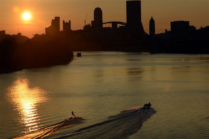 18_RendlemanBOP-8 A water skier travels on the Monongahela River as the sun sets over Pittsburgh in August.