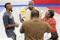 William Gay, left, his friend Carlos Rolle, center with hat, and Mr. Gay's brother Unrikay Hall chat with a community member as they hand out turkeys in November in Tallahassee, Fla.
