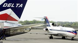 A Delta jet passes another plane on the tarmac at Hartsfield-Jackson Atlanta International Airport, where former a Delta employee suspected of smuggling firearms onto New York passenger jets worked as a baggage handler.