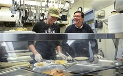 Julia Rendleman/Post-Gazette shot on Tuesday, December 23, 2014 Peter Smith/local Volunteers Cynthia Calkins and Mayor Bill Peduto serve Christmas meals Tuesday, Dec. 23 at Light of Life Rescue Mission on the North Side.