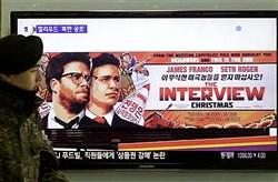 "A South Korean army soldier walks near a TV screen showing an advertisement of Sony Picture's ""The Interview"" on Monday."