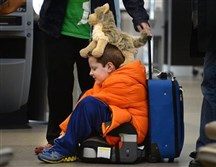 David Welborn, 7, sits in the lost luggage line at the Delta Airlines desk at the Raleigh-Durham International Airport Tuesday, with his trusty stuffed dog.