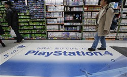 A shopper walks on the logo of Sony's PlayStation 4 at an electronics store in Tokyo on Christmas Day. Sony's online PlayStation store and Microsoft's Xbox site suffered disruptions to users on Christmas Day in the latest possible cyber-attacks on the companies.